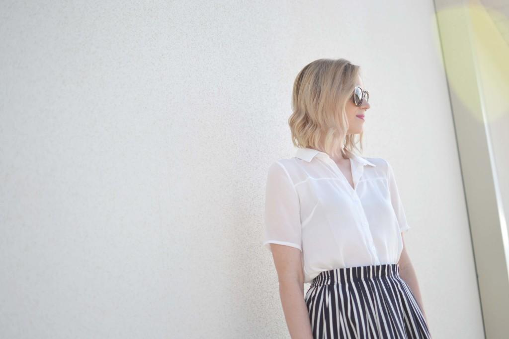 striped skirt, white blouse, karen walker sunglasses closeup sun flare