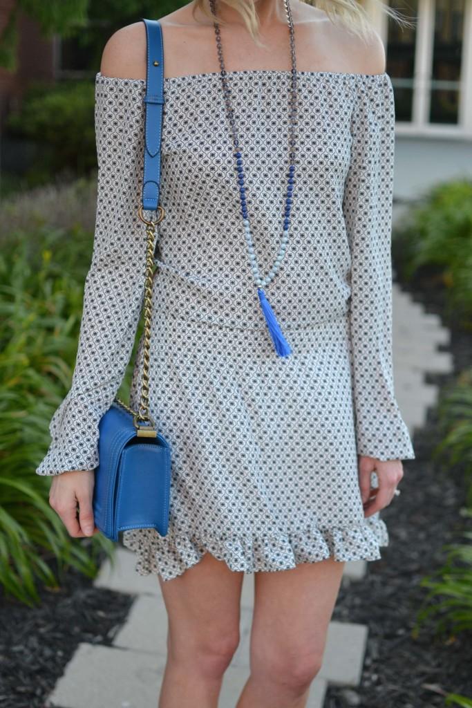 off the shoulder dress, blue bag, tassel necklace