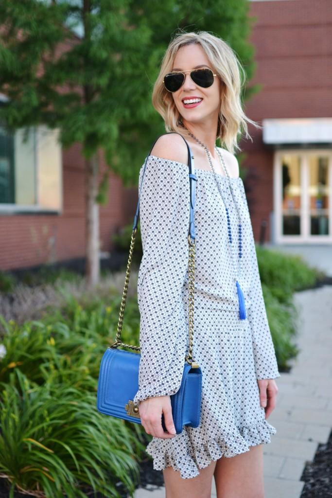 off the shoulder dress, tassel necklace, blue bag