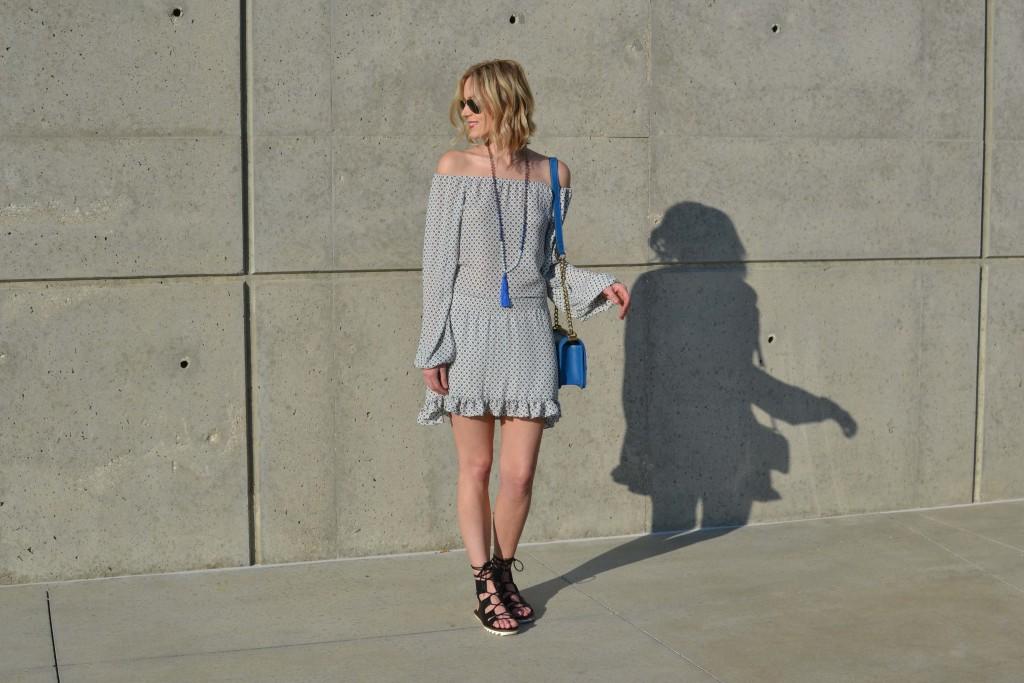 off the shoulder dress, tassel necklace, blue bag, lace up sandals