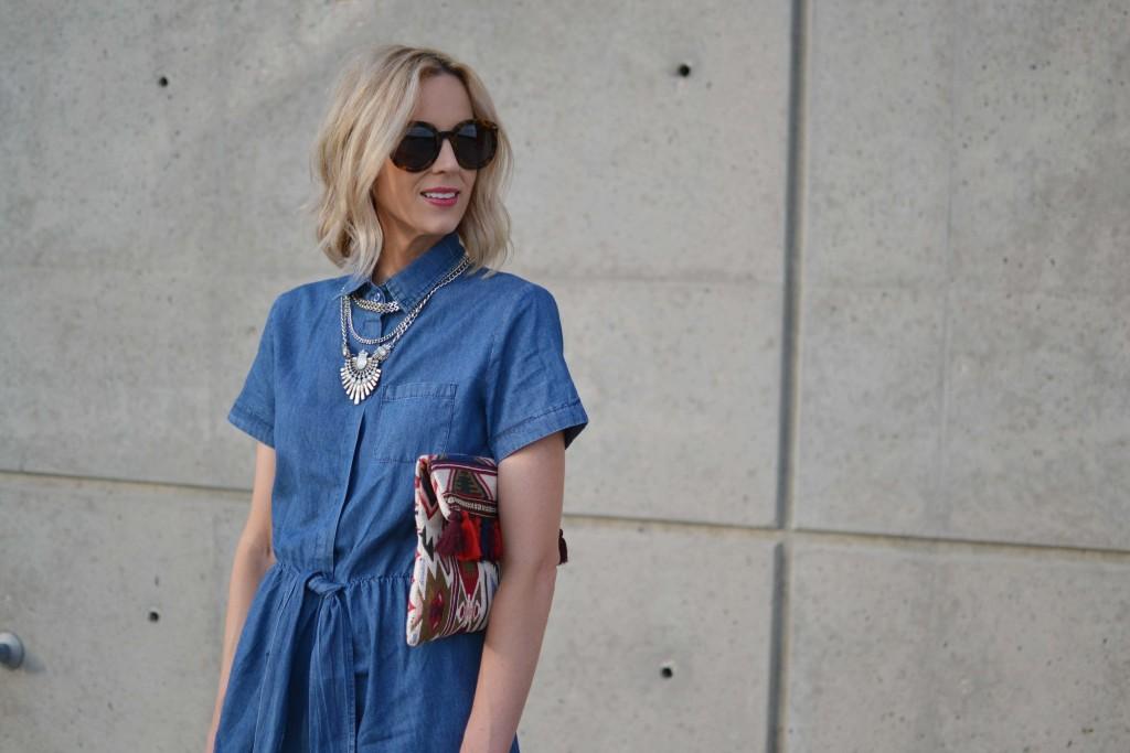 denim dress, clutch, karen walker sunglasses, silver necklace