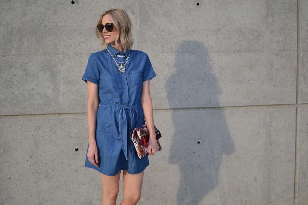 denim dress, fringe clutch, karen walker sunglasses, silver layer necklace