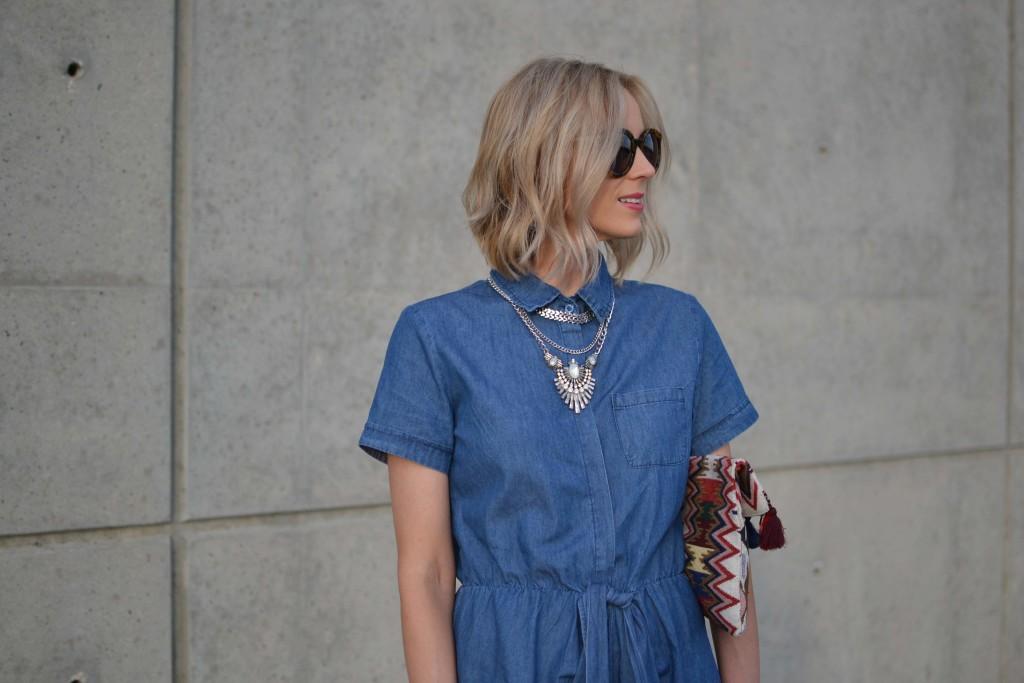 denim dress, fringe clutch, karen walker sunglasses, silver necklace