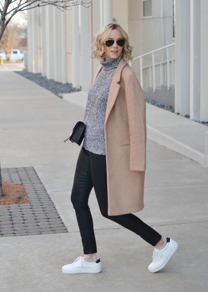 tan coat, grey turtleneck, coated black jeans, white flatform sneakers, black crossbody bag