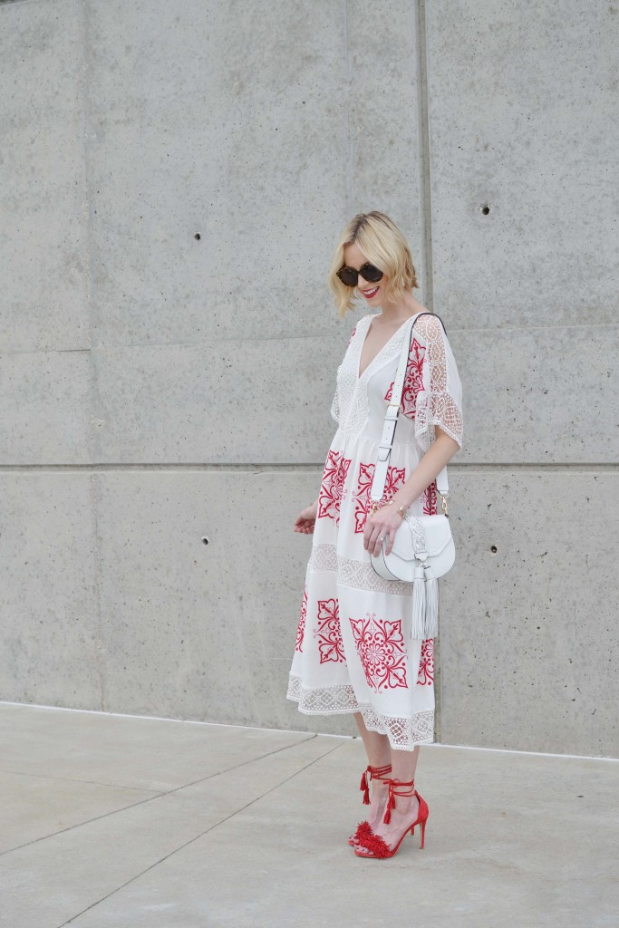 red and white embroidered midi dress, red lace up heels, white tassel purse