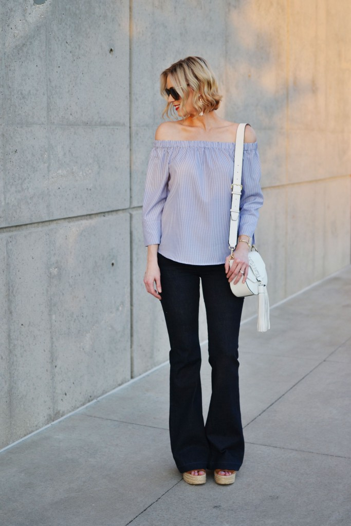 blue and white striped off the shoulder top, white tassel bag, flare jeans, wedges