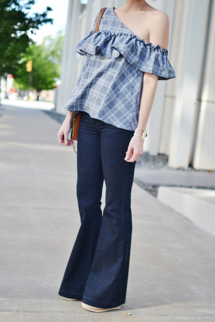 one shoulder ruffle top with flare jeans