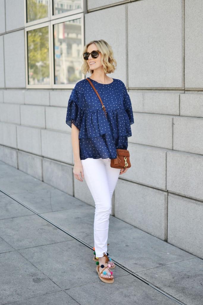 navy polka dot ruffle top, white jeans, pom pom sandals, tan Rebecca Minkoff bag
