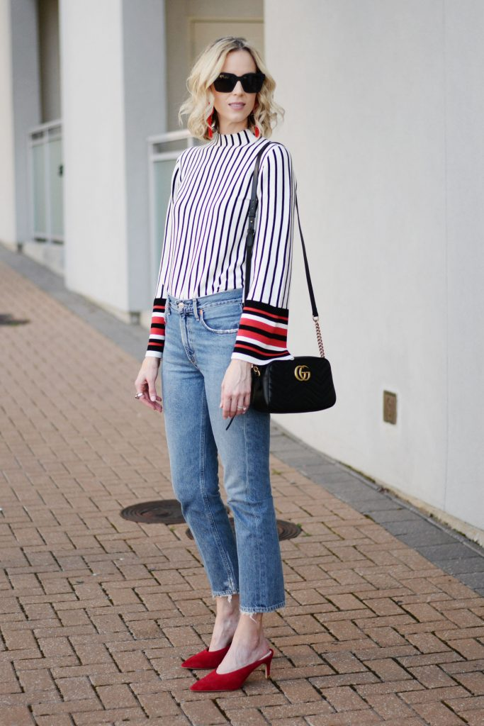 red and black bell sleeved top tucked into straight leg jeans, how to style straight leg jeans, red heeled mules, gucci marmont bag