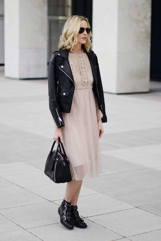 feminine and edgy outfit combination, tulle dress with leather moto jacket, black buckle boots, black aviators