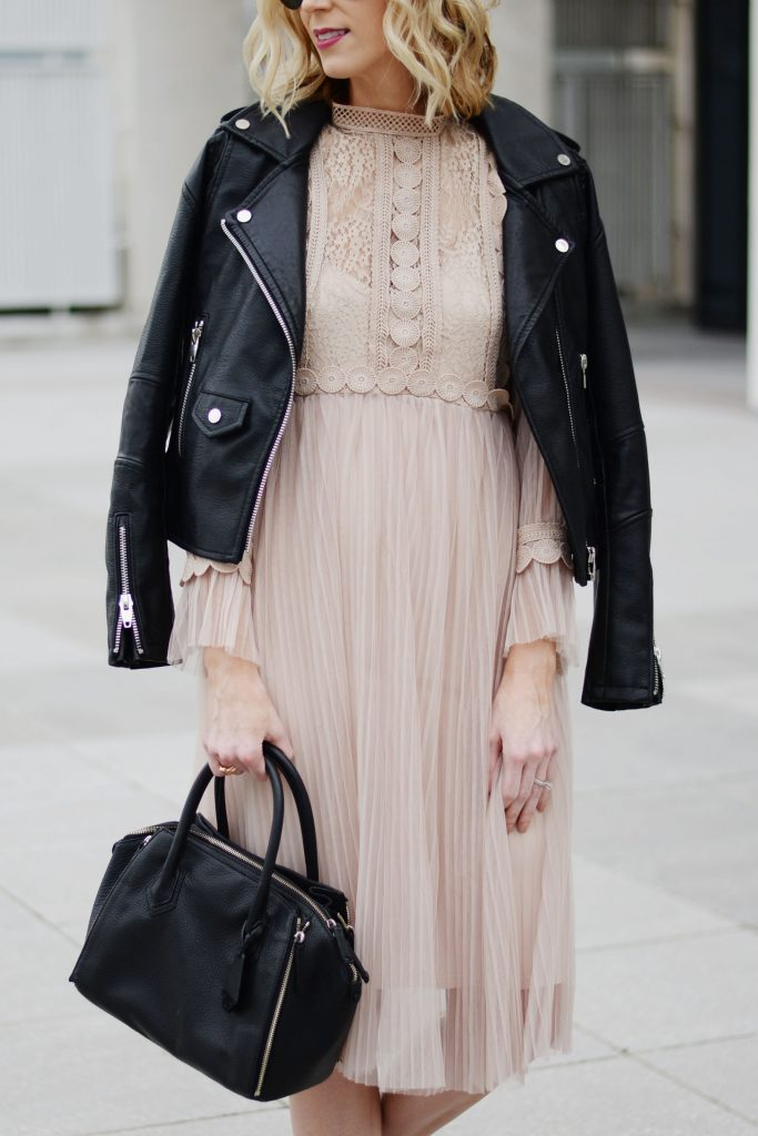 nude tulle dress with lace detailing, black leather moto jacket, black purse