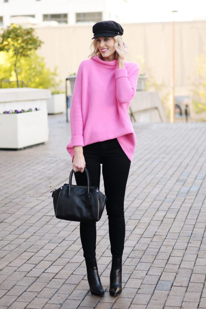 hot pink tunic sweater with black jeans and boots, baker boy hat