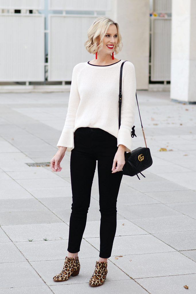 cream sweat, black jeans, leopard booties, red earrings