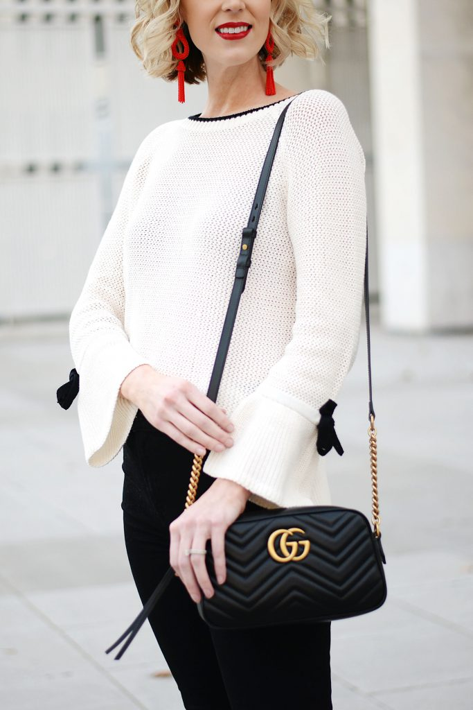 cream sweater with black bows, black jeans, red earrings, red lipstick, black gucci bag