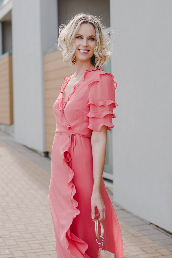 beautiful coral wrap dress with ruffle detail on sleeve and hem