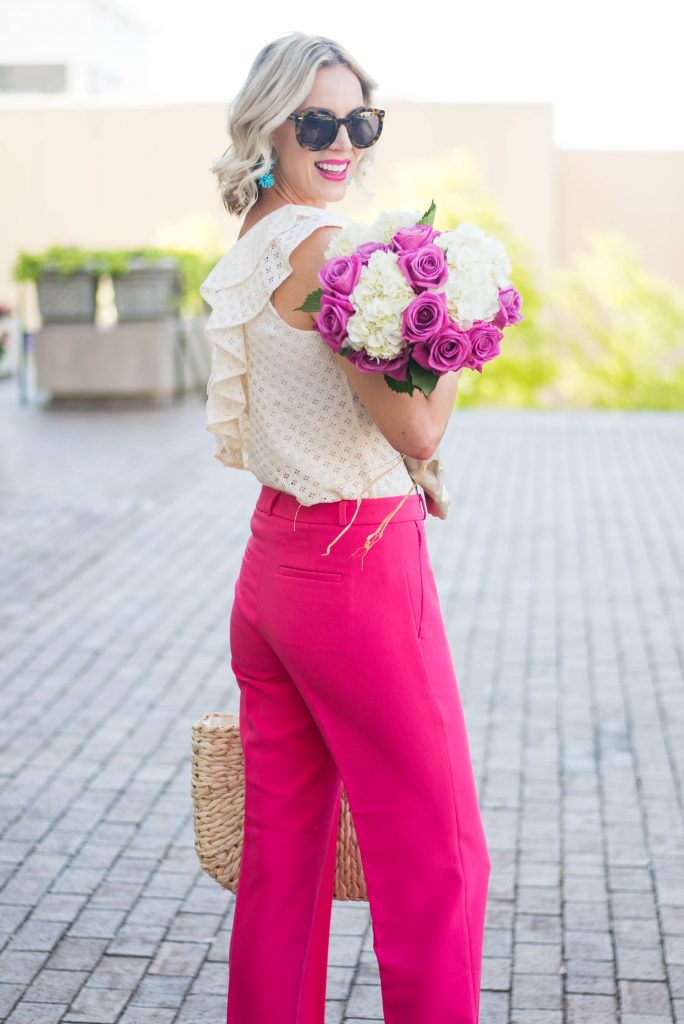 turquoise statement earrings with cream ruffle blouse and pink pants, flower bouquet