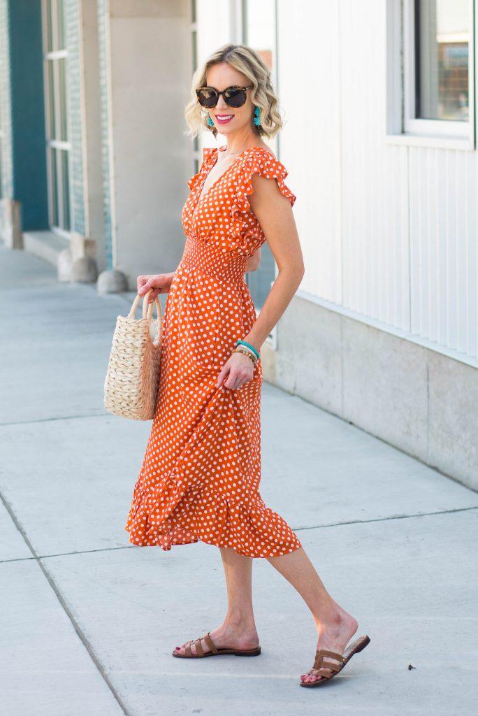 orange polka dot midi dress with ruffles, straw bag, turquoise accents