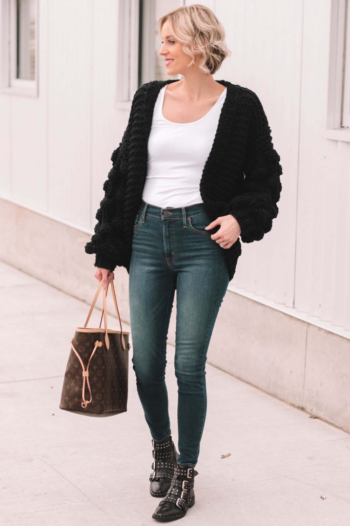 chunky knit black cardigan with black ankle boots and jeans