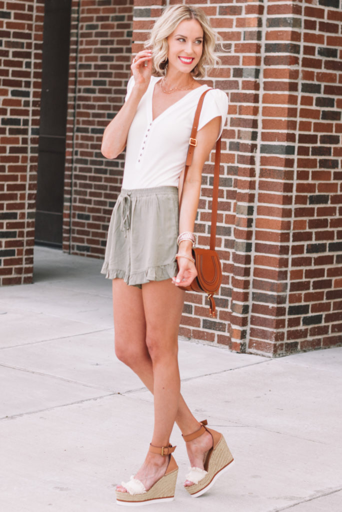 olive ruffle hem pull on shorts styled with a white henley bodysuit