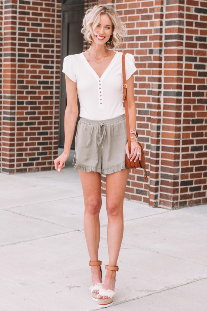 olive ruffle hem pull on shorts styled with a white henley bodysuit and wedges