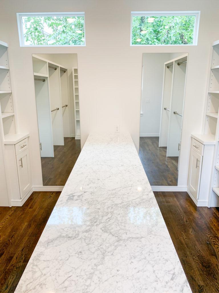 all white master closet dual mirrors and island