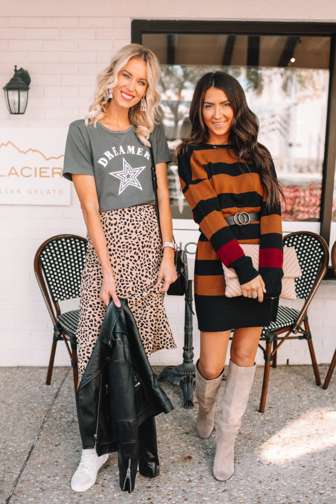 fall outfit ideas, blonde girl wearing leopard skirt and graphic tee, brunette in a sweater dress and boots