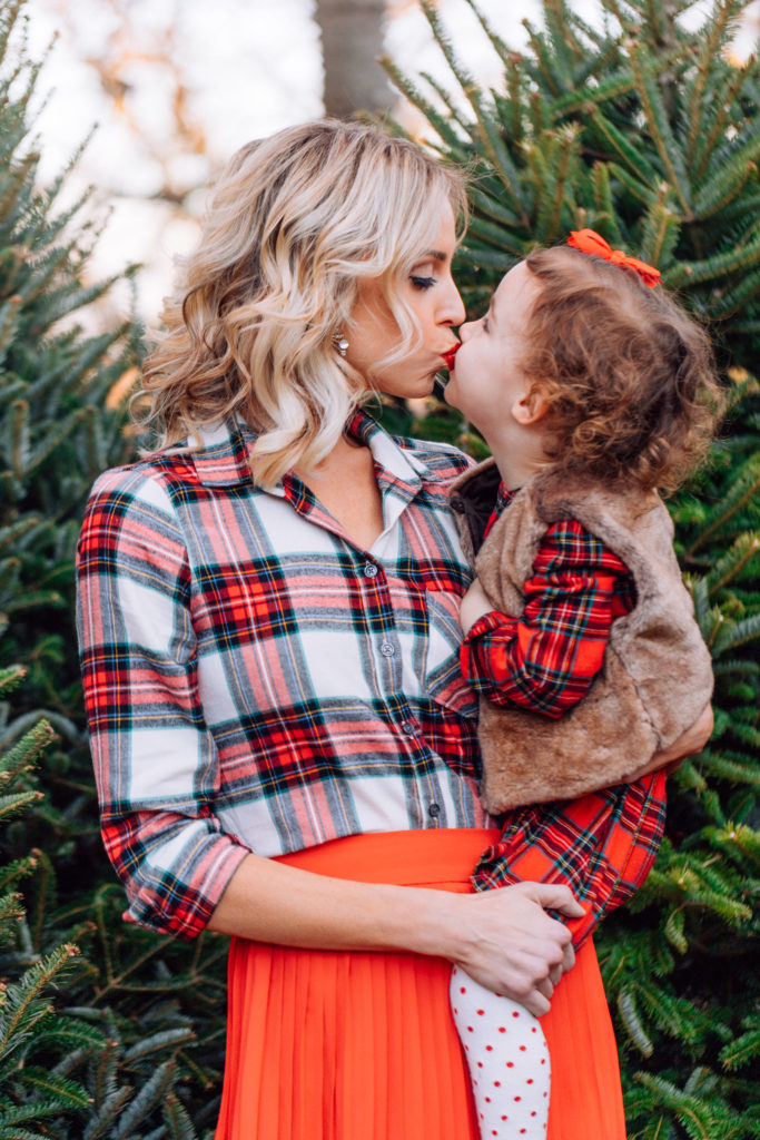 mom and daughter matching plaids, what to wear for family Christmas tree farm photos, Christmas flannel, Christmas plaid, red pleated midi skirt, faux fur vest