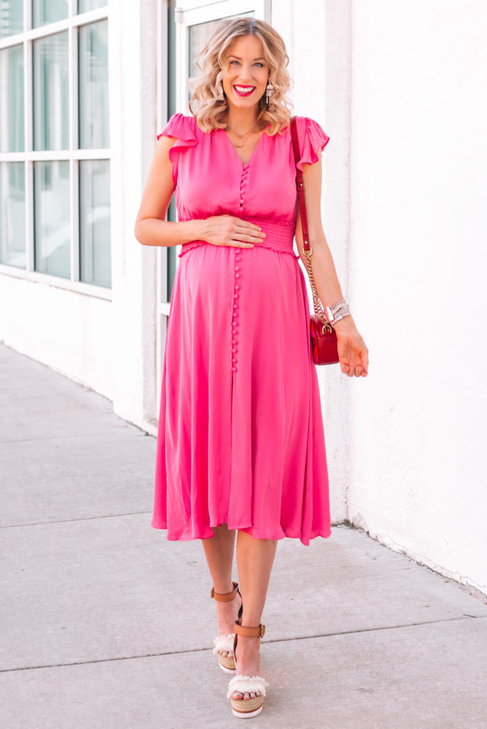 This is a gorgeous pink satin dress with a smocked waist and flutter sleeves. It would make the perfect pink girl baby shower dress.