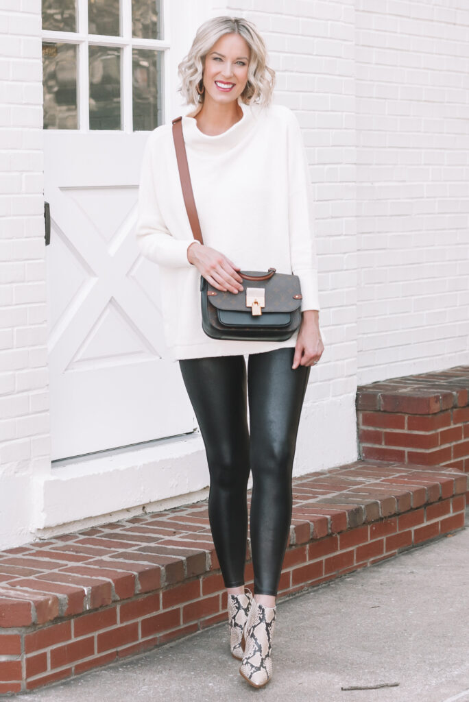 Cream tunic sweater paired with leather leggings and snakeskin boots.