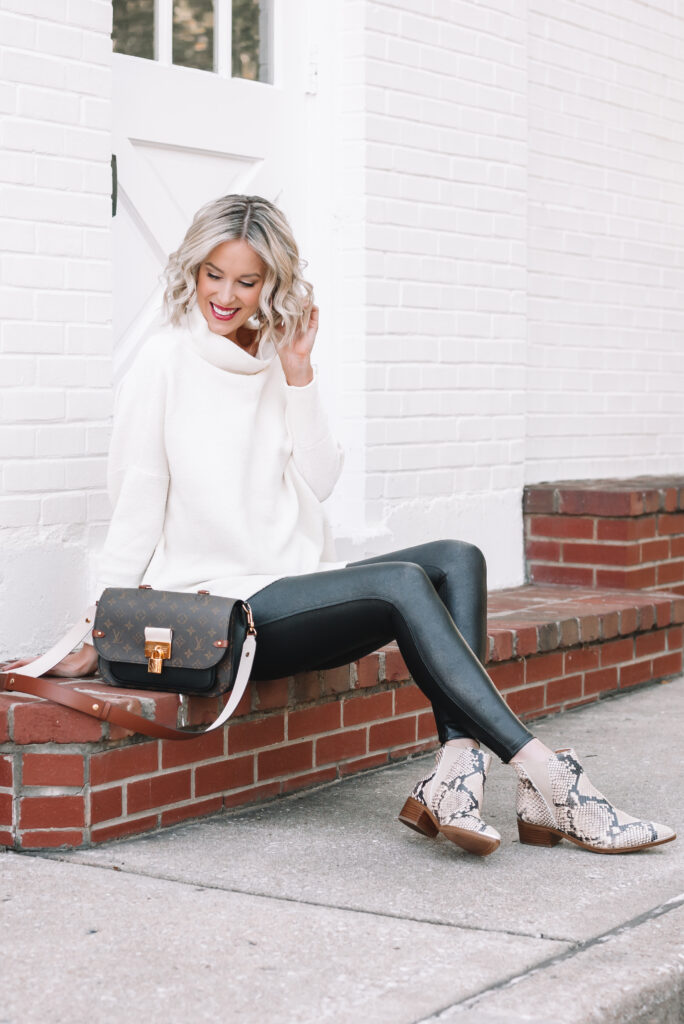 I love how this long white tunic sweater pairs with my leggings and snakeskin boots for the perfect faux leather leggings outfit!