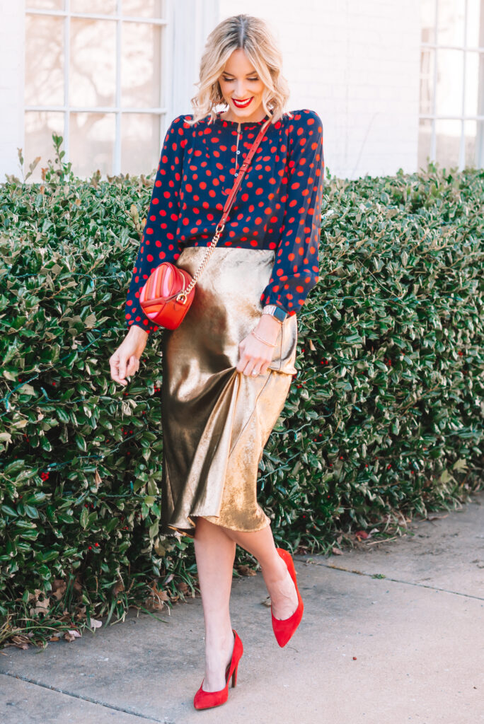 A printed blouse is the perfect pairing for a dressy gold midi skirt.