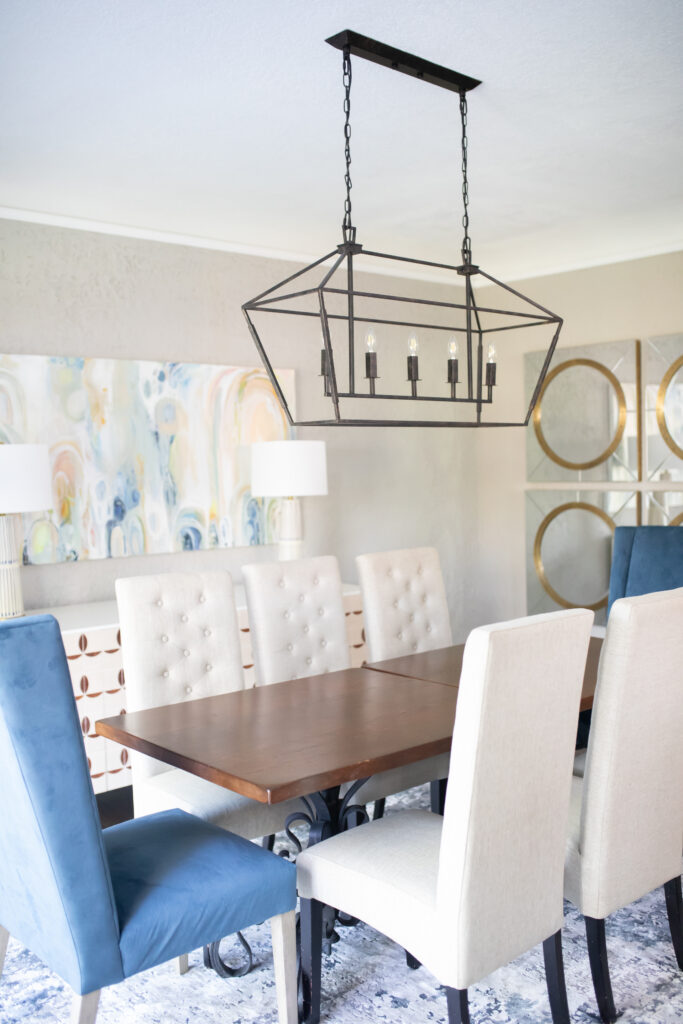 I've always wanted a light fixture that made a statement in our room! Our table is a long rectangle, and this type of long, rectangular chandelier is made to go over tables just like ours. It's a large, antique bronze iron chandelier perfect for our transitional eclectic dining room.