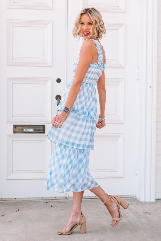 This is the most gorgeous blue gingham midi dress! It is true to size, has the most gorgeous smocking, tiers, and ruffle straps. I highly recommend it!! It would be the perfect wedding guest dress this summer.