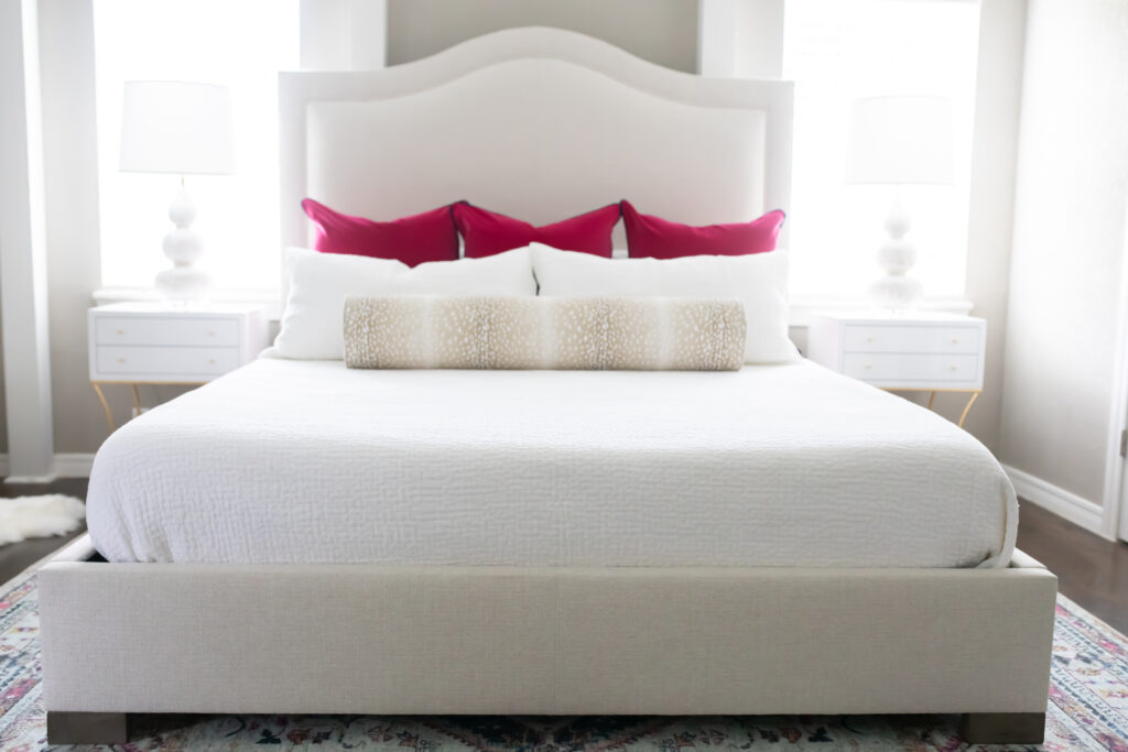 Sharing our transitional eclectic bedroom update with Luxe Furniture & Design. Our master bedroom is modern and bright with pops of color. I love this king size upholstered bed with white bedding, magenta pillows, and antelope bolster.