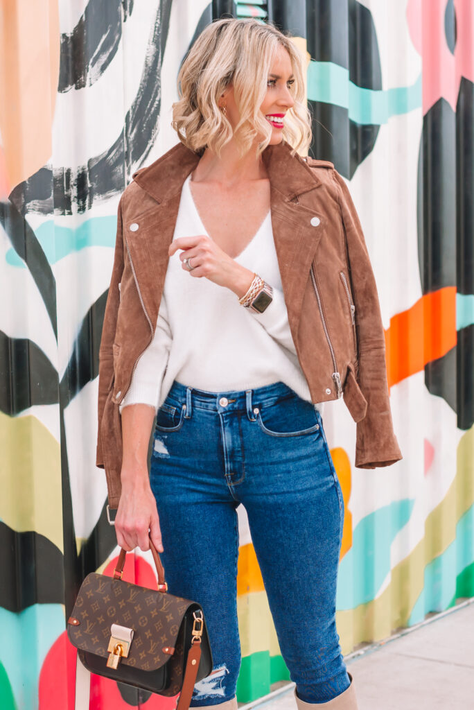 This fuzzy v-neck white sweater paired with a suede moto jacket and skinny jeans is a wardrobe classic!